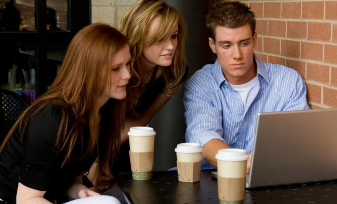 Pessoas em uma cafeteria em frente a um computador consumindo cafés